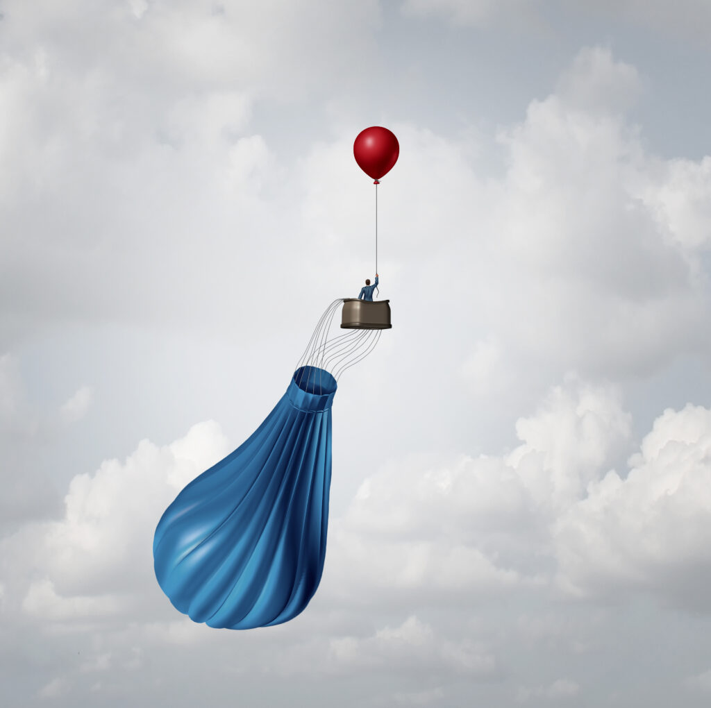 deflated-hot-air-balloon-with-basket-and-passenger-held-in-air-by-smaller-balloon