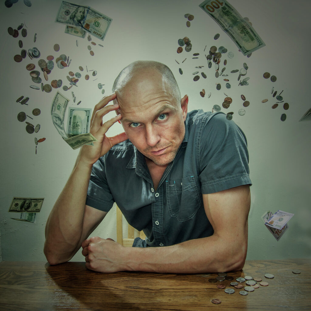 bald-man-in-grey-polo-holding-forehead-and-leaning-forward-on-table-with-cash-and-coin-money-digital-background