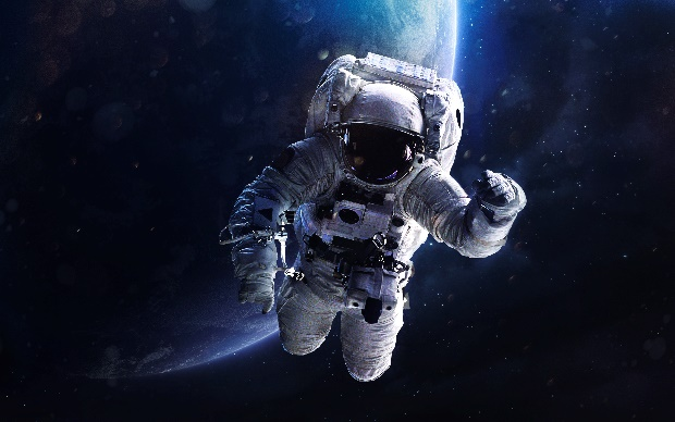 An astronaut on a spacewalk with Earth in the background. Innovation in manufacturing with the help of companies like PQ Ovens will help make space more accessible.