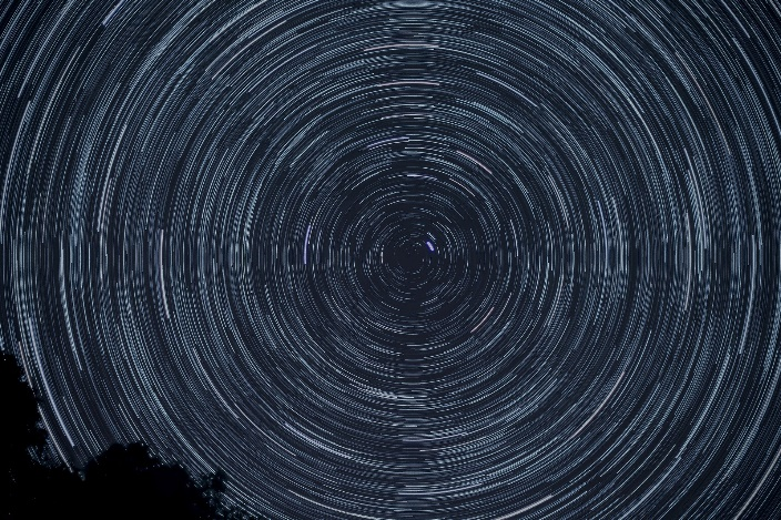 Time lapse astrophotograph showing stars swirling in the night sky as Earth rotates.